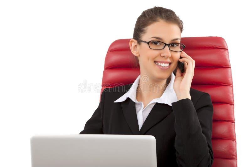 美丽的女商人谈话在手机坐一把红色椅子在办公室 库存图片