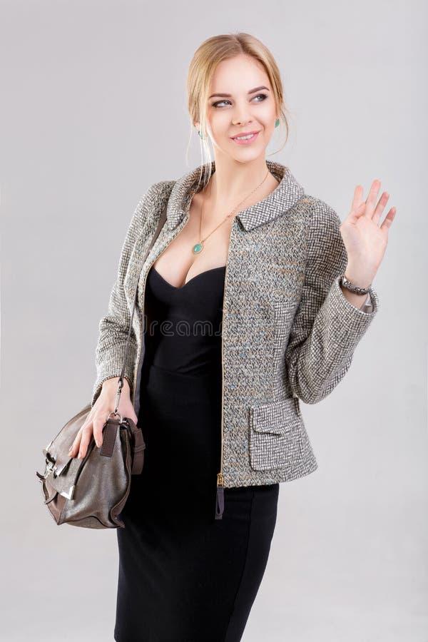 年轻美丽的女商人金发碧眼的女人画象黑礼服的和有在灰色背景的袋子的 免版税库存照片