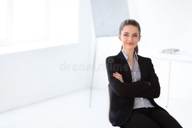 年轻美丽的女商人画象坐在t的椅子 免版税库存图片