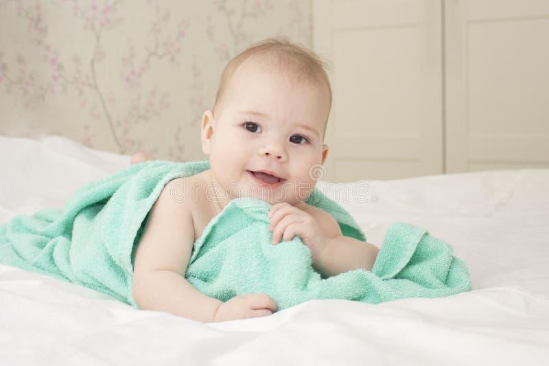 美丽的女婴使用与毛巾的6个月在沐浴以后 笑的愉快的儿童正面 童颜软的焦点 免版税库存照片