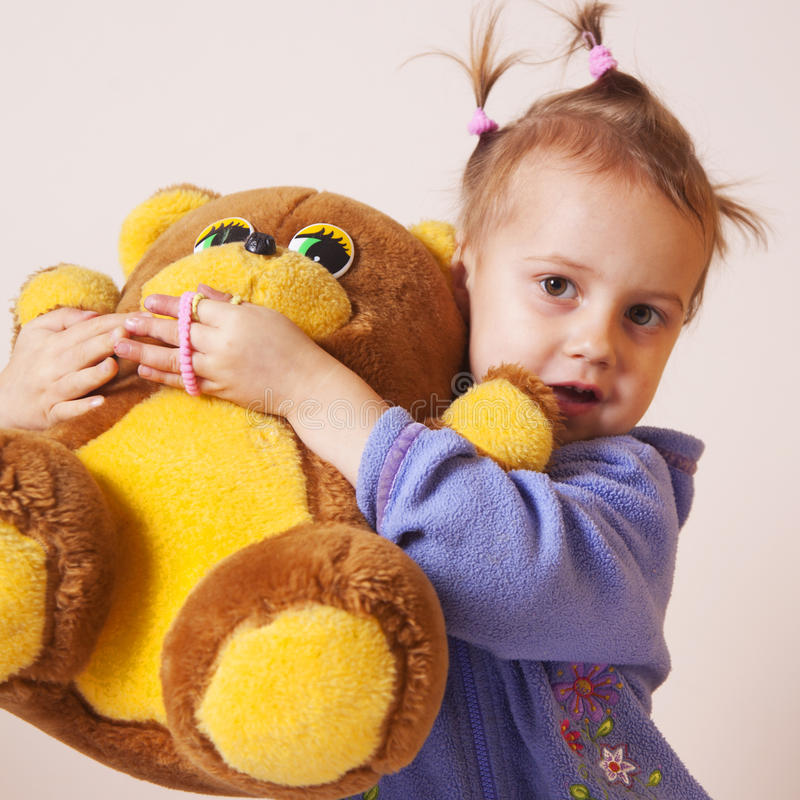 美丽的女婴使用与玩具熊童年的,喜悦, s 库存照片