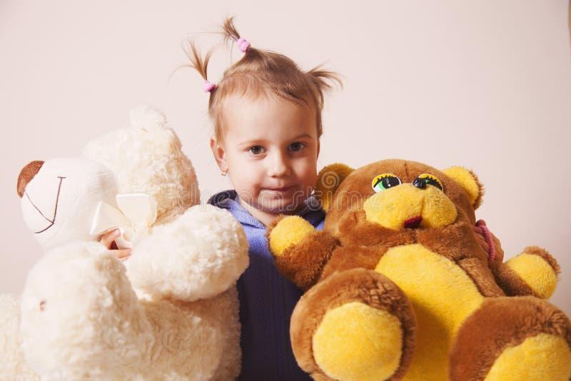 美丽的女婴使用与玩具熊童年的,喜悦, s 免版税库存照片
