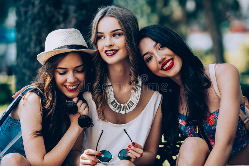美丽的女孩一偷听谈话三二个年轻人 免版税库存图片