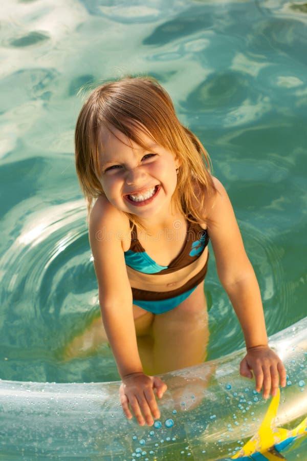 美丽的女孩一点池微笑的游泳 库存图片