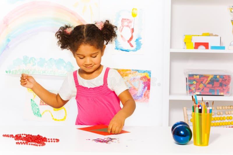 美丽的女孩制作与Xmas树的纸盒卡片 免版税库存图片