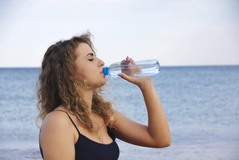 美丽的女孩卷发喝从海瓶的水 免版税库存图片
