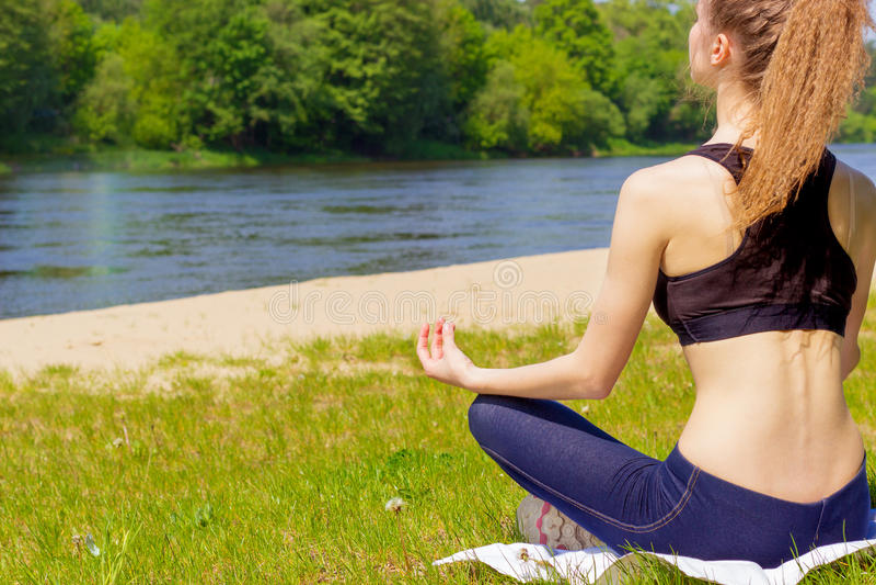 美丽的女孩参与体育,瑜伽,在海滩的健身由河在一个晴朗的夏日 库存图片
