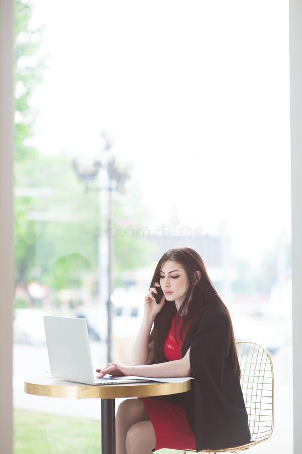 美丽的女孩叫由坐在与膝上型计算机的桌上的手机在餐馆 库存图片