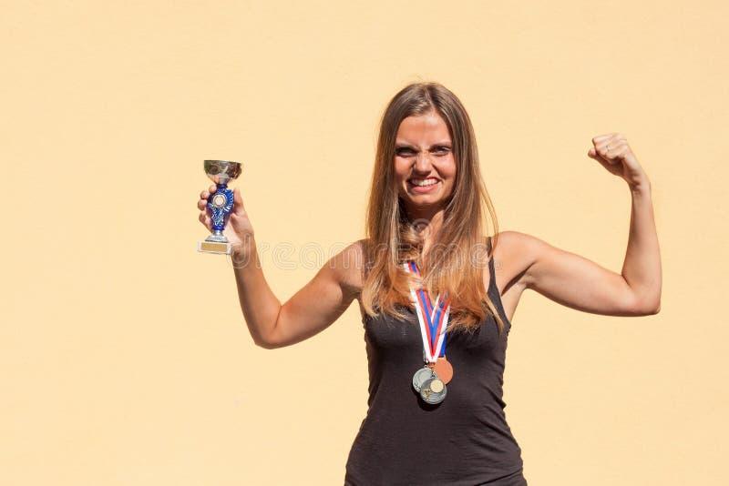 美丽的女孩和体育奖牌 体育冠军 体育成就的奖 免版税图库摄影