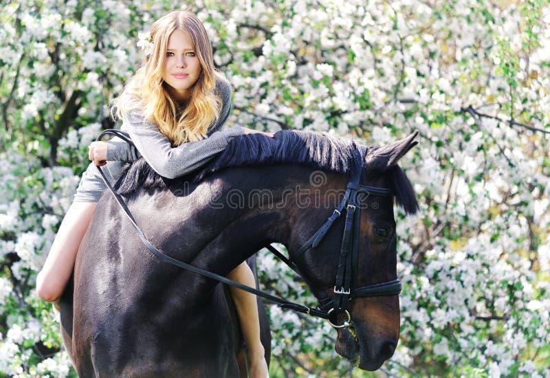 美丽的女孩和马在春天庭院里 免版税库存照片