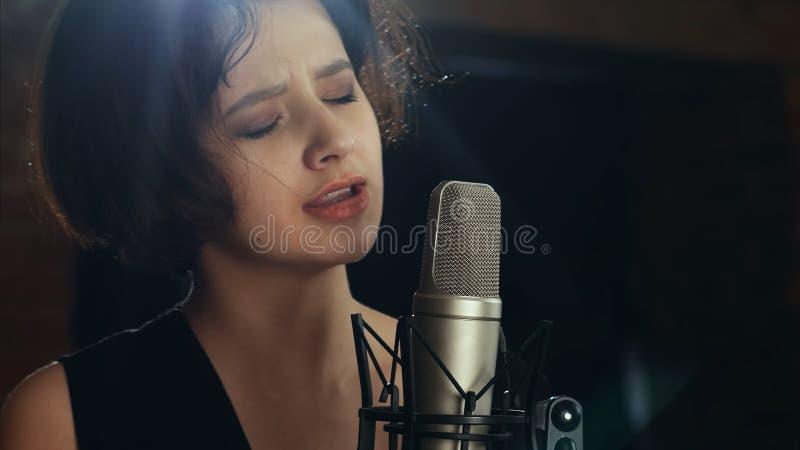 美丽的女孩唱歌入在咖啡馆的一个话筒 库存照片