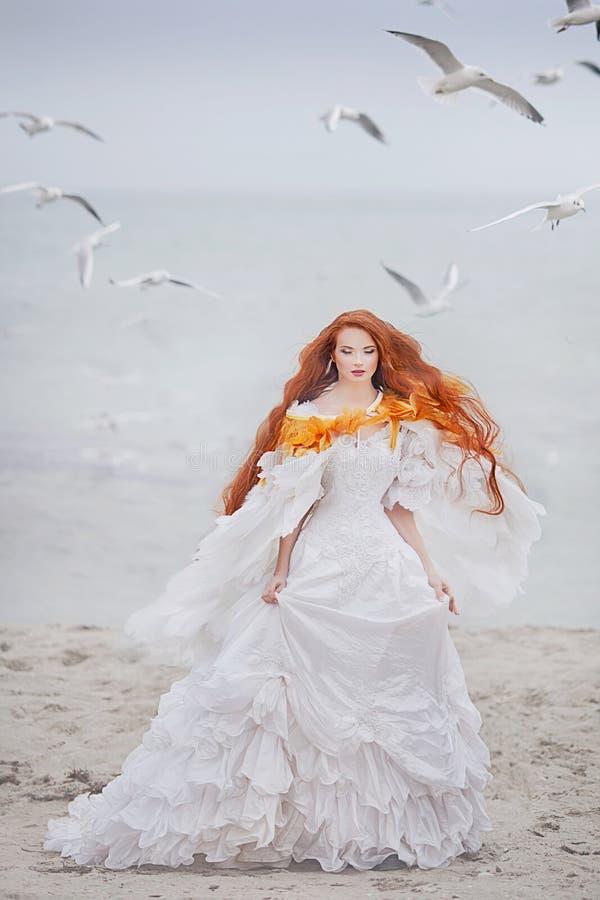 美丽的女孩喜欢在海滩的一只天鹅 免版税库存照片