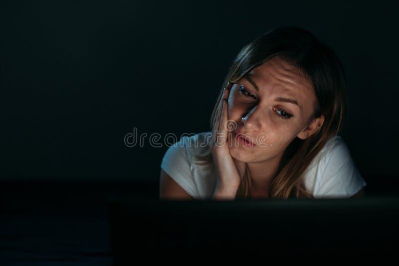 美丽的女孩困窘看膝上型计算机 库存图片