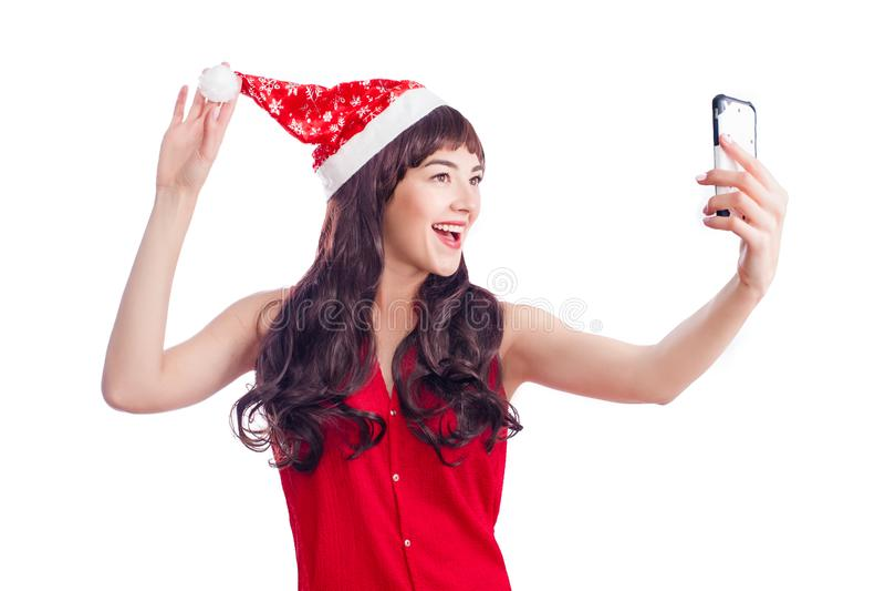 美丽的女孩圣诞节画象  戴圣诞老人帽子的少年 微笑和做selfie的女孩在手机 免版税库存图片