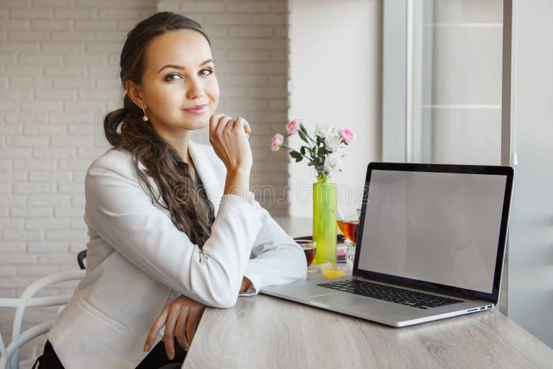 美丽的女孩在与膝上型计算机的桌倾斜她的手肘 免版税库存图片