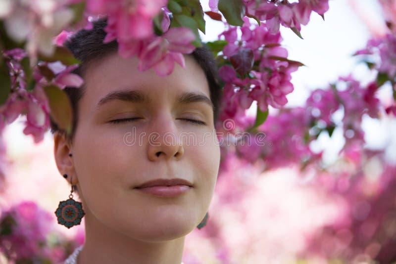 美丽的女孩在公园享用桃红色开花的树 库存照片