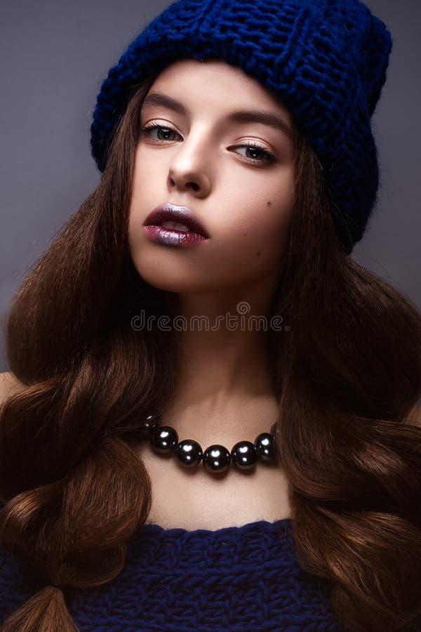 美丽的女孩在冬天编织了与项链的帽子蓝色颜色在珍珠的脖子上 与精美构成和s的年轻模型 图库摄影