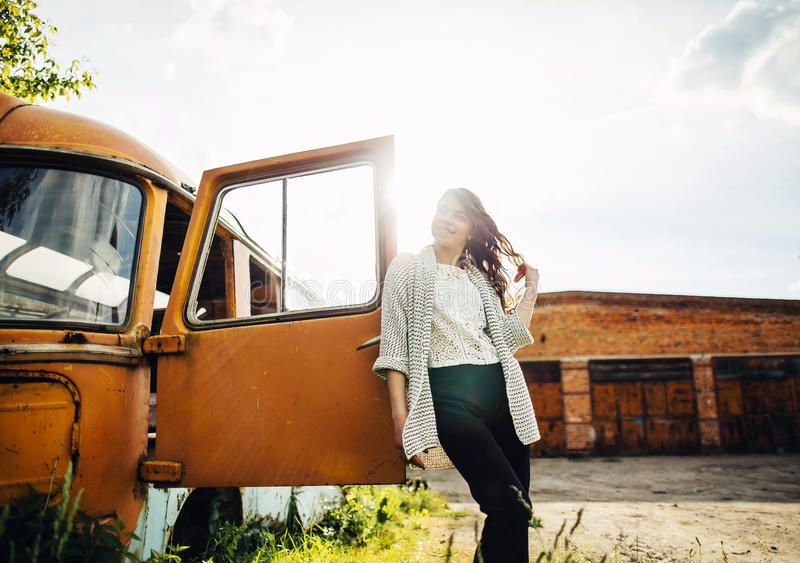 美丽的女孩在减速火箭的汽车附近摆在 库存图片