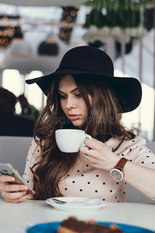 美丽的女孩在咖啡馆坐 免版税库存照片