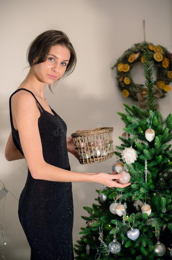 美丽的女孩在圣诞节前装饰一棵圣诞树 库存图片