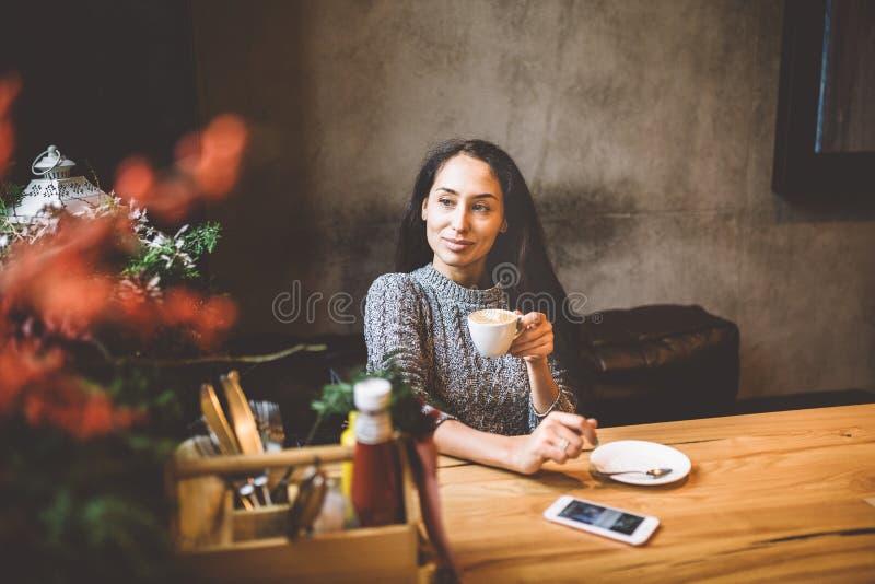 美丽的女孩在她的在用圣诞节装饰装饰的咖啡馆的手机旁边喝从一个白色杯子的咖啡, 库存图片