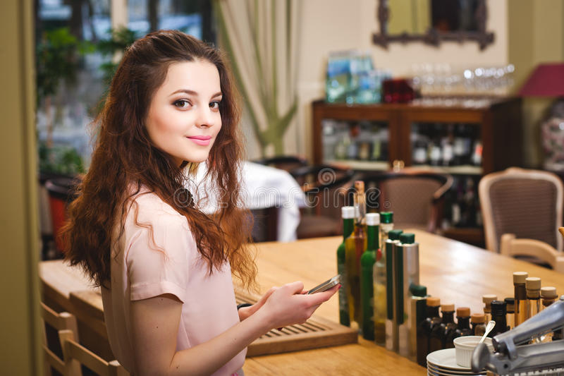 年轻美丽的女孩在家看电话在厨房里 图库摄影
