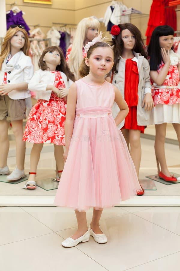 美丽的女孩在尝试在一件桃红色礼服的商店 图库摄影