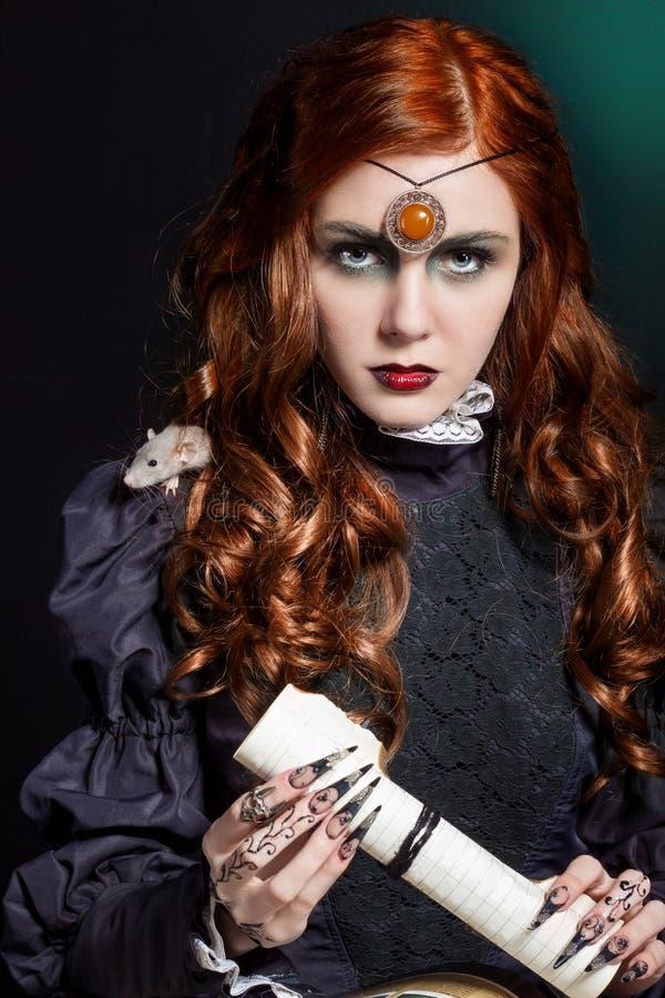 美丽的女孩在巫婆的图象的长的头发方式下有老鼠的在他的肩膀,与明亮的黑长的错误钉子 库存图片