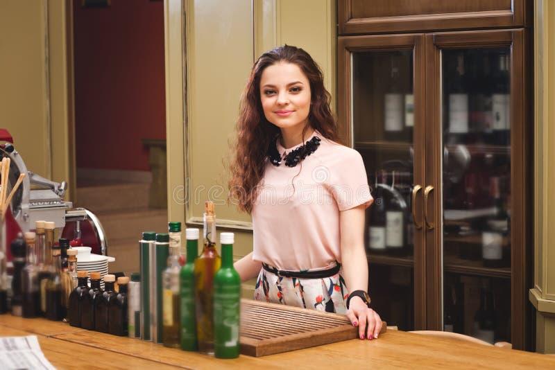 年轻美丽的女孩在意大利样式的厨房里站立 免版税库存照片