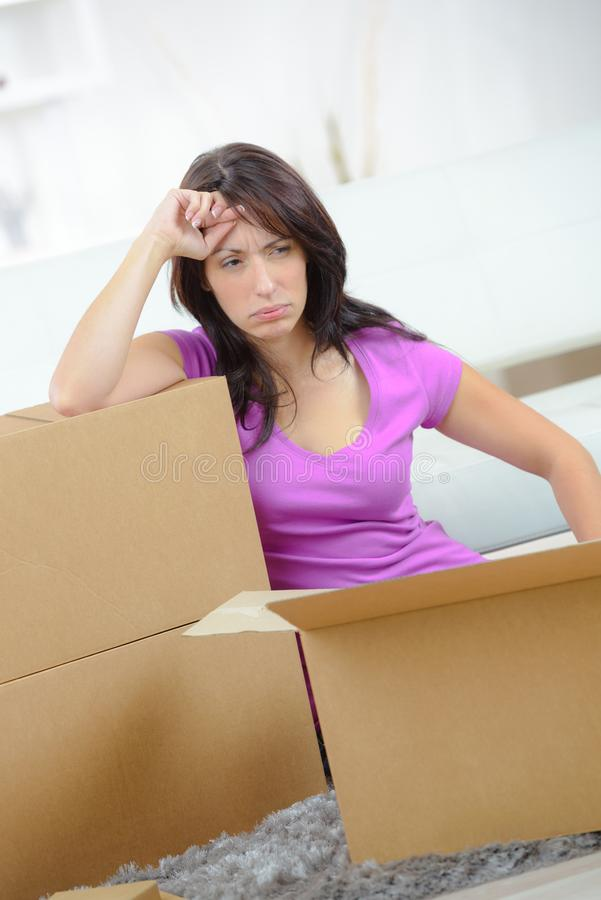 美丽的女孩在新的家疲倦了移动的箱子 免版税图库摄影