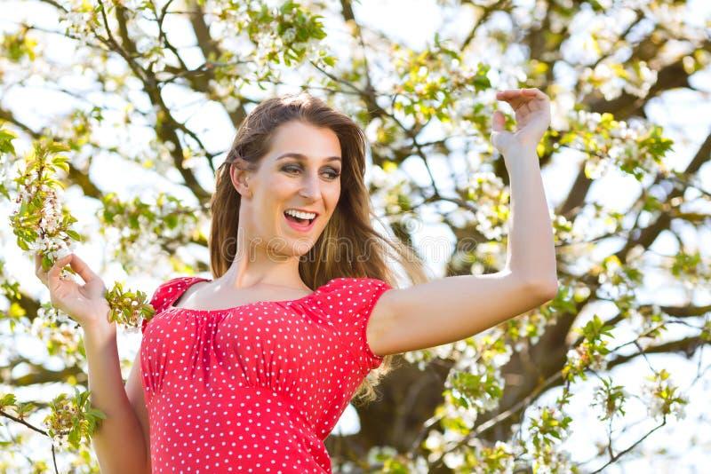 春天和树开花的女孩 免版税库存照片