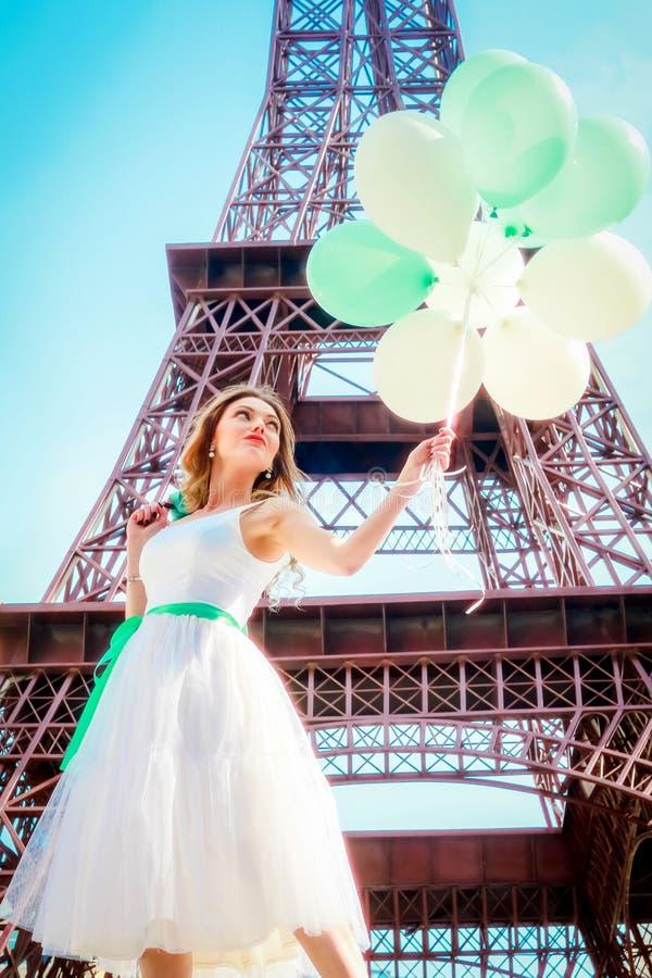 美丽的女孩在有埃佛尔铁塔的巴黎在背景 一件浪漫礼服的女孩有气球的在手上 库存照片