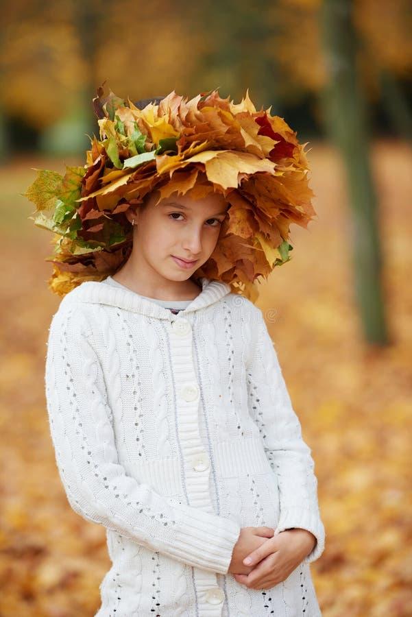 美丽的女孩在有花圈的秋天公园  免版税库存照片