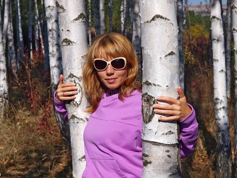 美丽的女孩在桦树森林里 库存照片