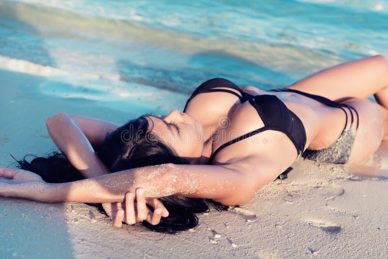 美丽的女孩在沙子海滩的水中 免版税库存图片