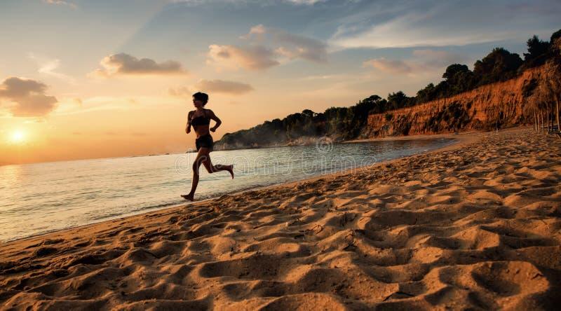 美丽的女孩在海滩跑步 免版税库存图片
