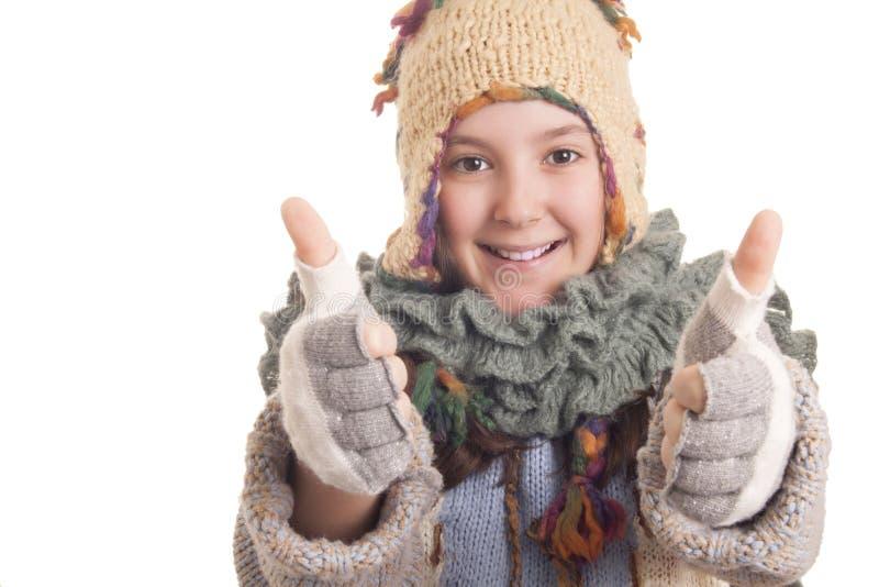 美丽的女孩在温暖的冬天给显示赞许穿衣 库存照片