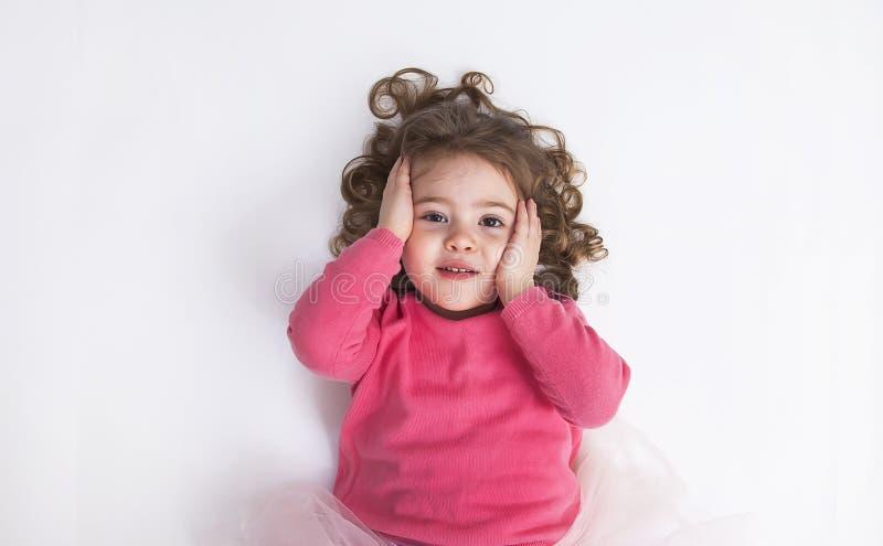 美丽的女孩在白色地板和微笑上说谎 免版税库存图片
