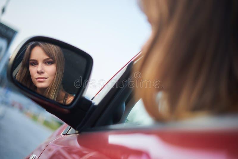 美丽的女孩在看在镜子的汽车坐 免版税图库摄影
