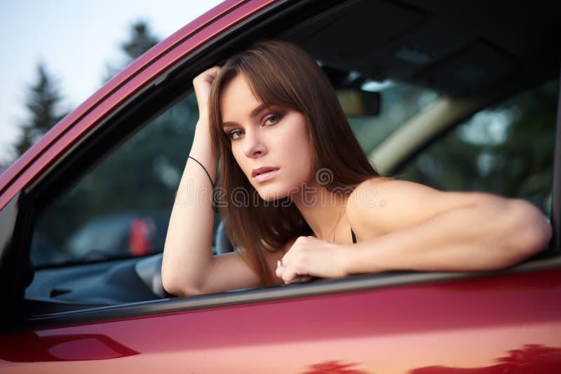 美丽的女孩在看的轮子后坐  免版税库存图片