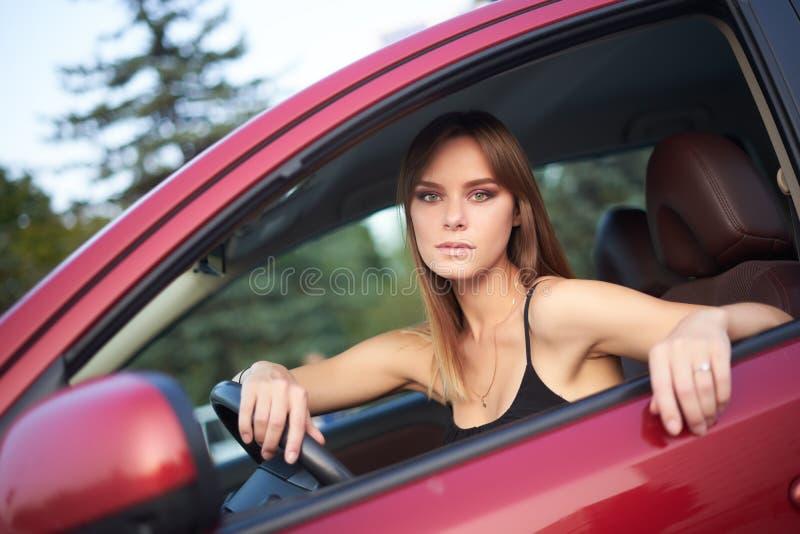 美丽的女孩在看的轮子后坐  库存照片