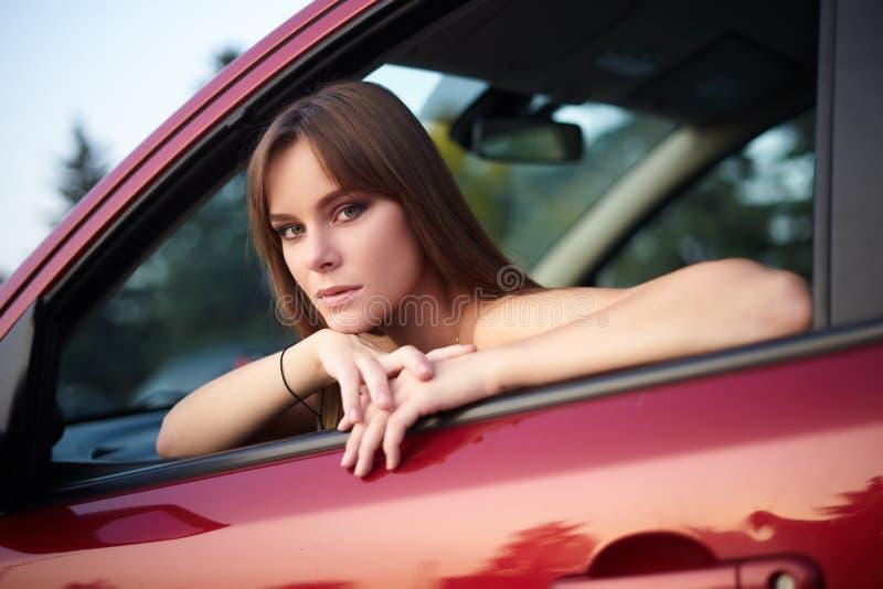 美丽的女孩在看的轮子后坐  库存图片
