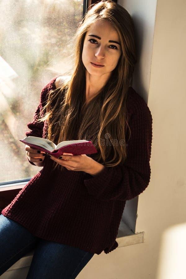 美丽的女孩在窗口和拿着圣经附近站立 库存照片