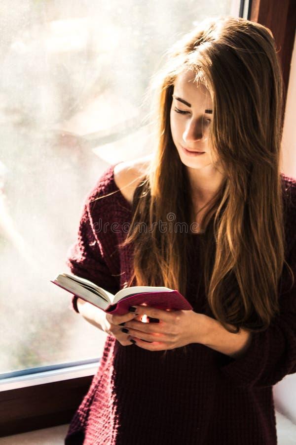 美丽的女孩在窗口附近站立并且读圣经 免版税图库摄影