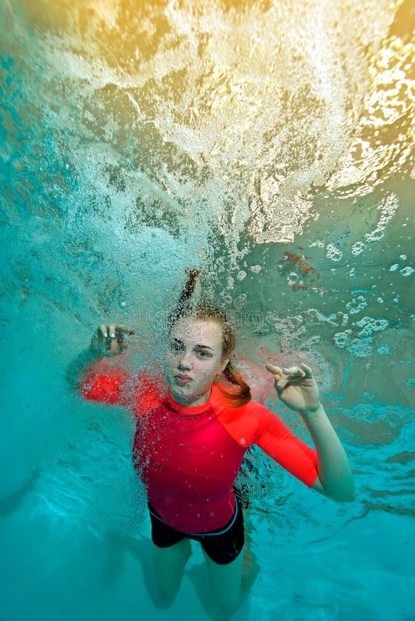 美丽的女孩在背景的红色泳装游泳在水面下在泡影的太阳光芒和看我 从u的底视图 免版税库存照片