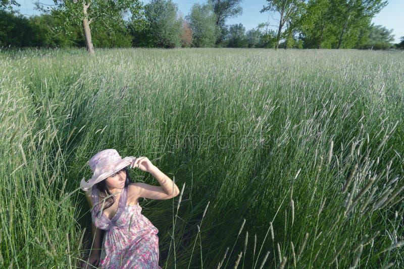 美丽的女孩在高草在春天草甸坐晴天 库存照片