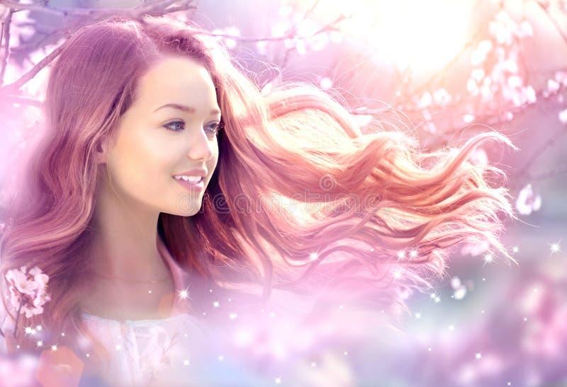 美丽的女孩在幻想春天庭院里 免版税图库摄影