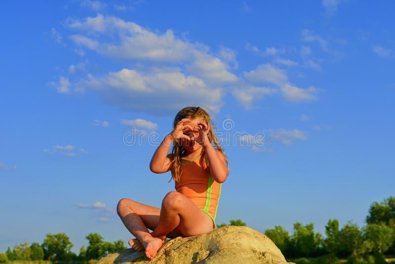 美丽的女孩坐一个大岩石 小女孩穿泳装 女孩由她的手做心脏形状姿态 免版税库存图片