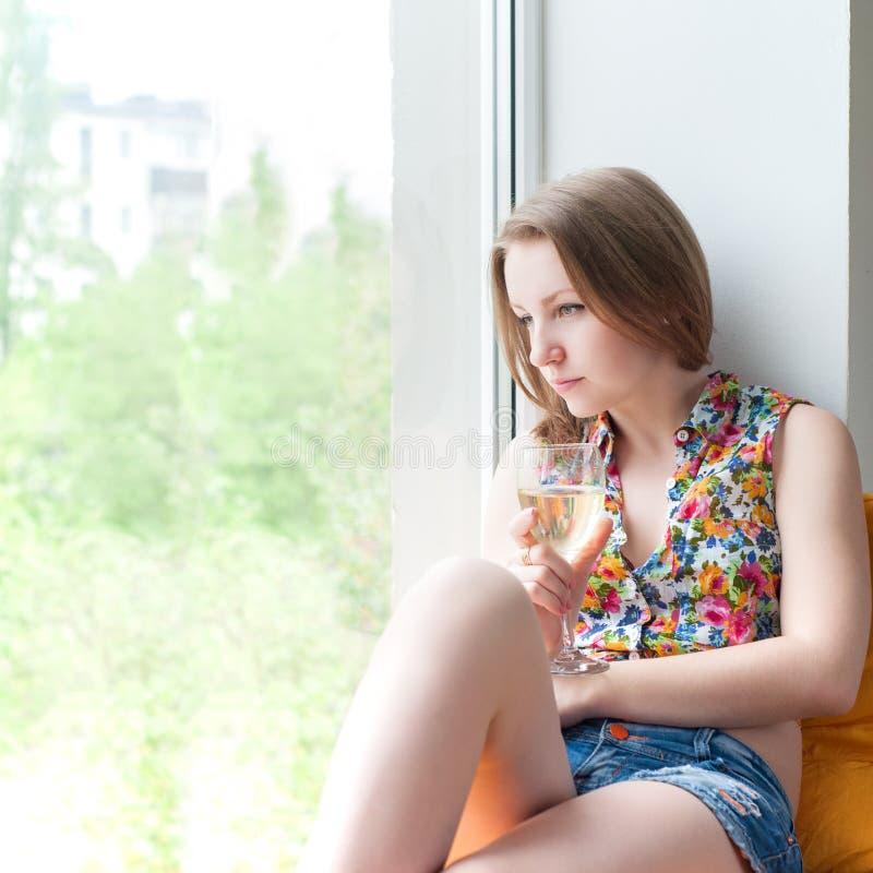 美丽的女孩坐与电话的窗口 免版税库存照片