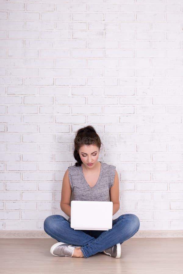美丽的女孩坐与膝上型计算机的在w的地板和空间 免版税图库摄影